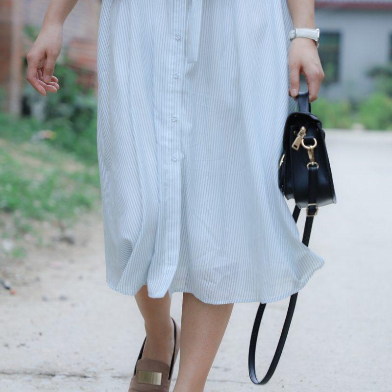 Kvinde går rundt i kjole med taske